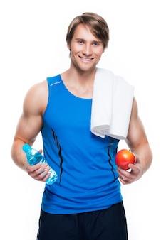 Il ritratto dello sportivo felice bello in camicia blu tiene l'acqua e la mela sopra la parete bianca.