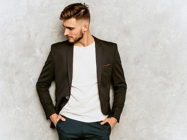 Portrait of handsome hipster   businessman model wearing casual black suit.