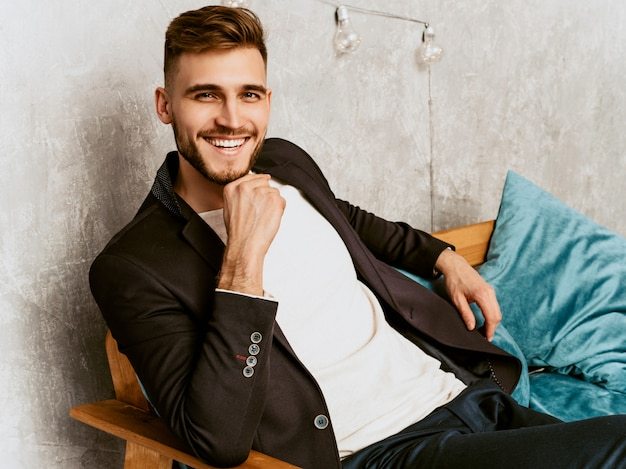 Portrait of handsome hipster  businessman model wearing casual black suit.