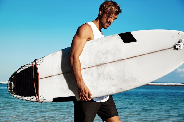Portrait of handsome hipster sunbathed fashion man model surfer wearing casual clothes going with surfboard on blue ocean and sky