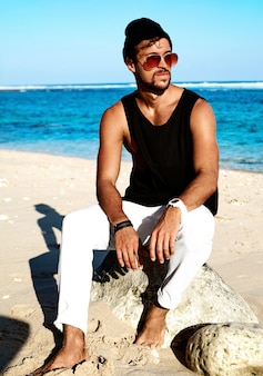 Portrait of handsome hipster sunbathed fashion man model wearing casual clothes in black t-shirt and sunglasses sitting on rocks