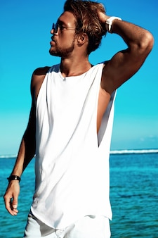 Portrait of handsome hipster sunbathed fashion man model wearing casual clothes in white t-shirt and sunglasses posing on blue ocean and sky