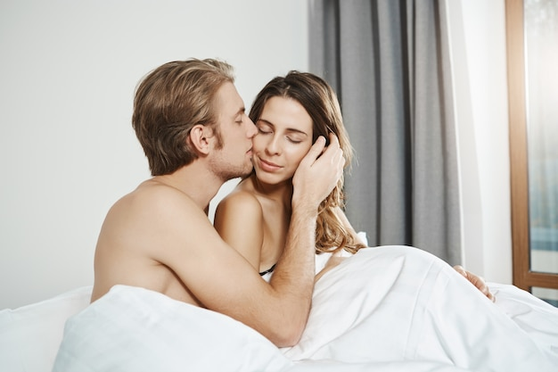 Portrait of handsome husband gently kissing his attractive wife in cheek while lying together in bed in daytime. couple cuddling while in bedroom, having forgot about everything that surround them