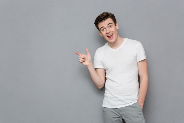 Portrait of handsome inspired attractive casual male in white t-shirt and gray pants pointing away on copyspace