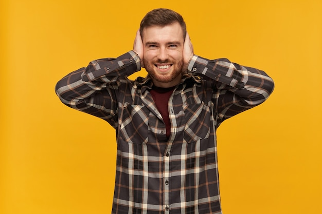 Portrait of handsome, joyful male with brunette hair and bristle. wearing checkered shirt and accessories. cover ears with palms. can't hear.  isolated over yellow wall