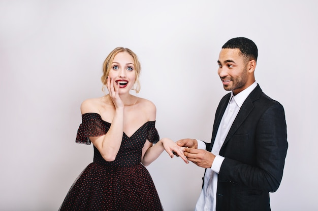 Портрет красивый радостный мужчина в белой рубашке, делающий предложение руки и сердца привлекательной удивленной молодой женщине в роскошном вечернем платье. праздник, валентинки, влюбленные вместе.