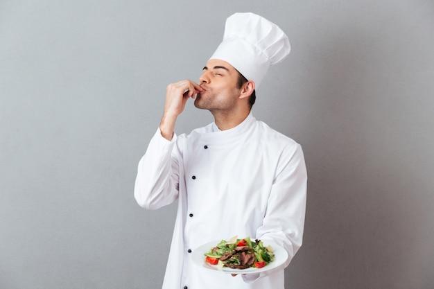Il ritratto di un cuoco unico maschio bello si è vestito in uniforme