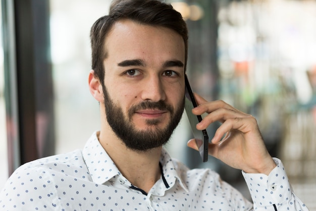 Portrait handsome male talking over phone