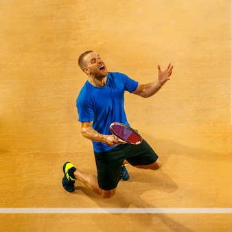 Ritratto di un giocatore di tennis maschio bello che celebra il suo successo su una parete della corte