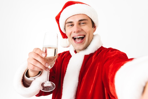 Portrait of handsome man 30s in santa claus costume and red hat taking selfie photo while holding glass with champagne