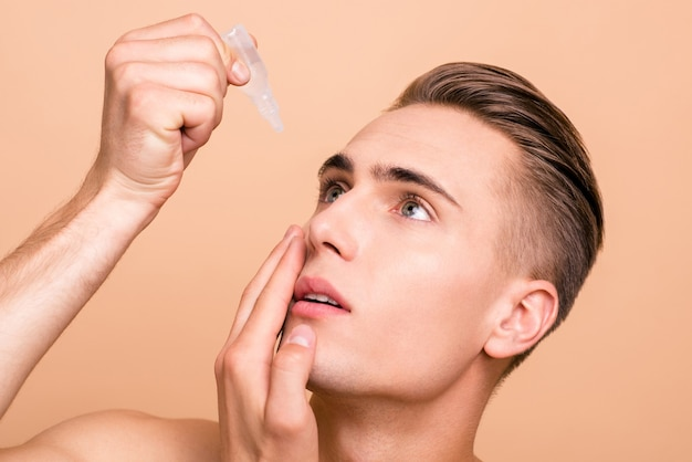 Portrait of handsome man applying eye drop isolated on pastel beige
