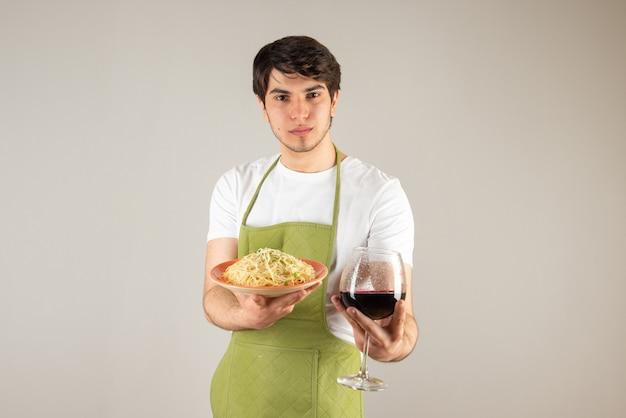 Ritratto di un bell'uomo in grembiule che tiene in mano un piatto con noodles e un bicchiere di vino.