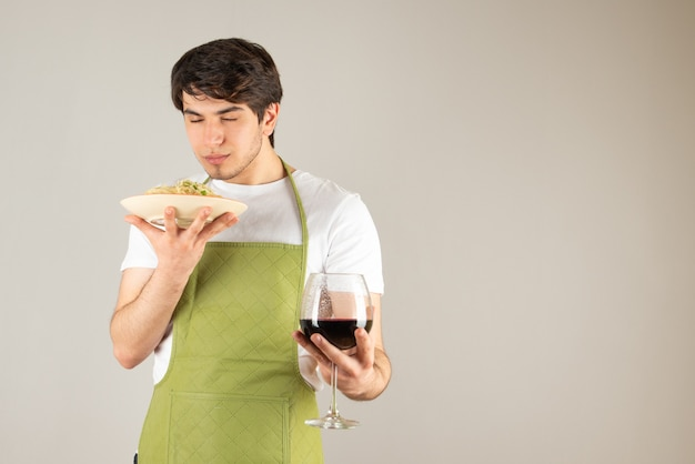Portrait of a handsome man in apron holding a plate with noodles and a glass of wine.