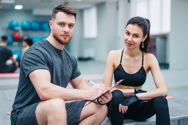 Portrait of a handsome man and attractive woman resting after workout and looking into camera in sports gym.