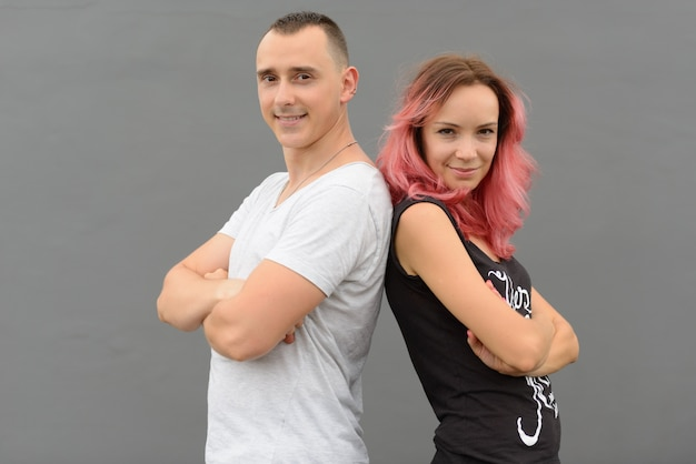 Portrait of handsome man and beautiful woman with pink hair as couple together and in love against gray wall outdoors