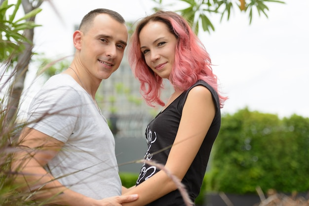 Portrait of handsome man and beautiful woman with pink hair as couple together and in love in the park outdoors