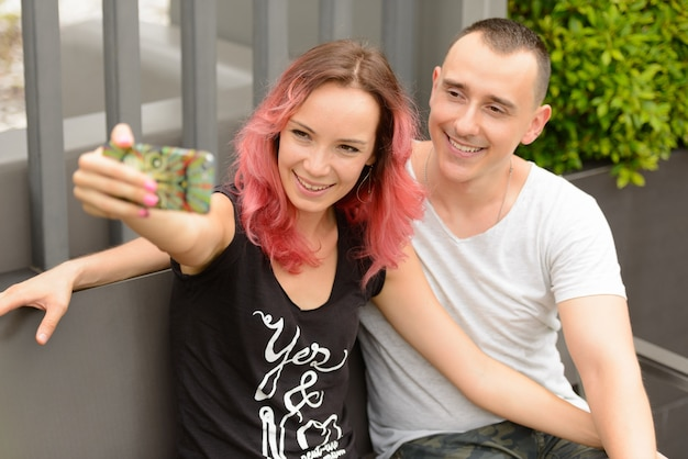Portrait of handsome man and beautiful woman with pink hair as couple together and in love at the park outdoors