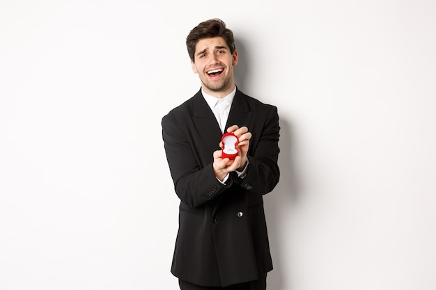 Portrait of handsome man in black suit, open box with wedding ring, making a proposal, asking to marry him, standing against white background.