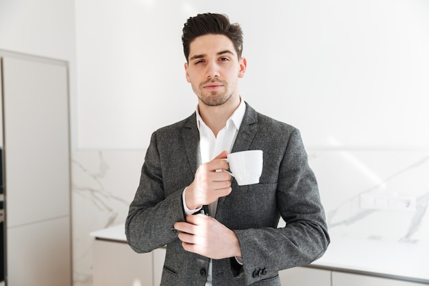 Portrait of handsome man in businesslike clothes looking on camera, and holding cup of coffee on lunch time at home