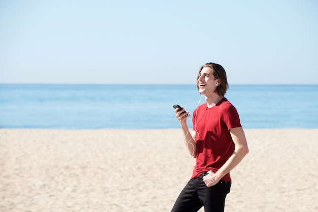 Portrait of handsome man by sea with smart phone and headphones