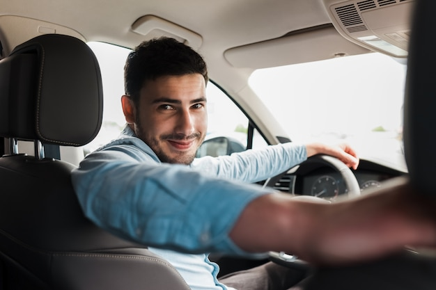 Portrait of handsome man in car