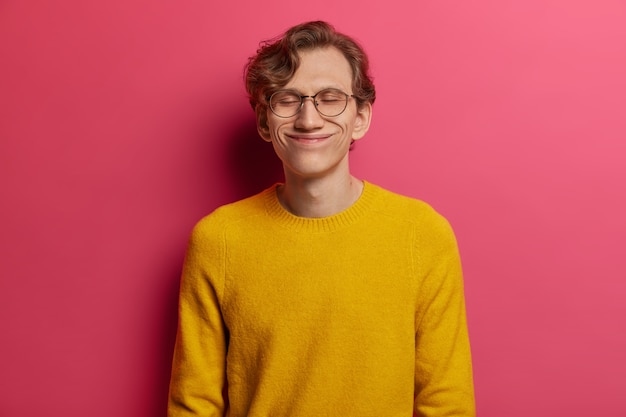 Portrait of handsome man closes eyes with pleasure, pleased to hear praising words from employer, has funny face, wears big optical glasses and yellow sweater, never stops dreaming, stands relieved