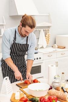 Portrait of handsome man cutting tomato