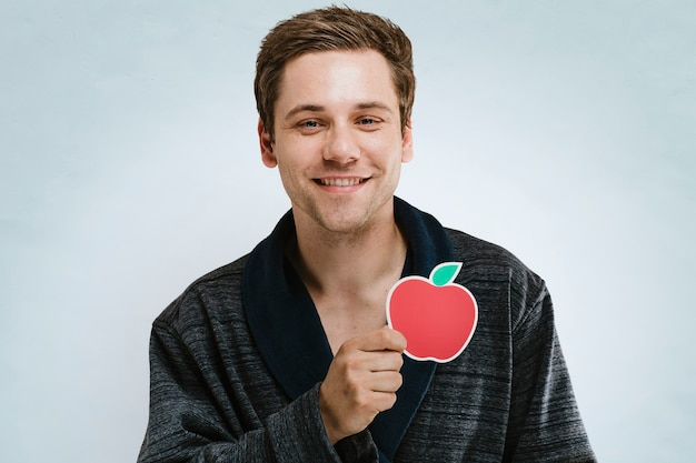 Portrait of a handsome man in a dark rope showing a red apple symbol