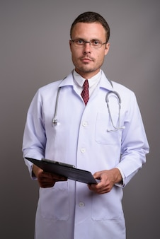 Portrait of handsome man doctor on gray