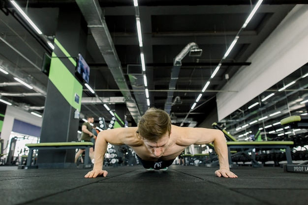 Portrait of a handsome man doing push ups exercise in fitness gym