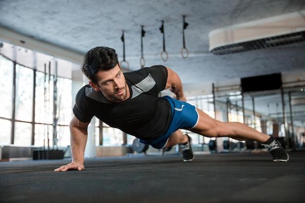 Portrait of a handsome man doing push ups