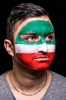 Ritratto di uomo bello faccia sostenitore fan della nazionale iraniana con bandiera dipinta faccia isolata su sfondo nero. fans le emozioni.