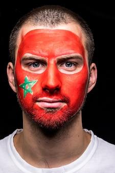 Ritratto di uomo bello faccia tifoso tifoso della nazionale del marocco con bandiera dipinta faccia isolata su sfondo nero. fans le emozioni.