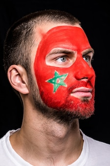Portrait of handsome man face supporter fan of morocco national team with painted flag face isolated on black background. fans emotions.
