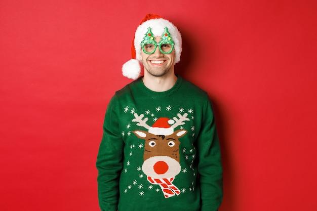 Ritratto di un bell'uomo con un maglione natalizio verde, cappello da babbo natale e occhiali da festa, sorridente felice, in piedi su sfondo rosso.
