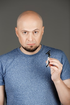 Portrait of handsome man in grey shirt holding razor over dark wall