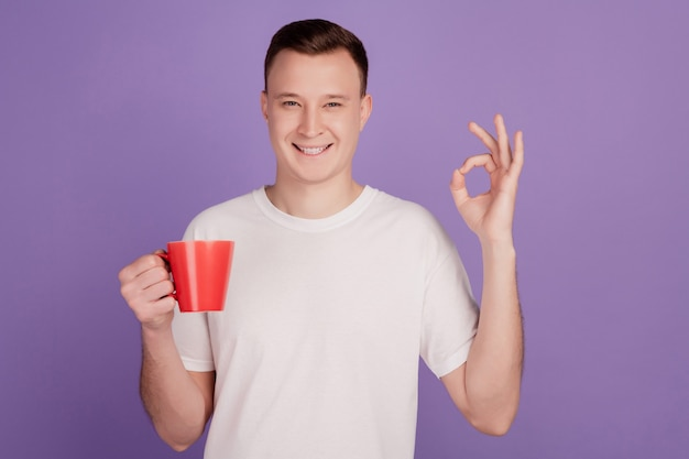 Portrait of handsome man hold cellphone coffee cup show okey gesture on purple background