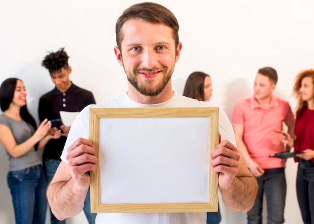 Portrait of a handsome man holding empty picture frame looking at camera