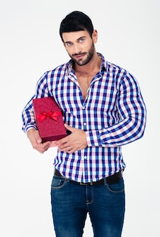 Portrait of a handsome man holding gift box isolated on a white wall