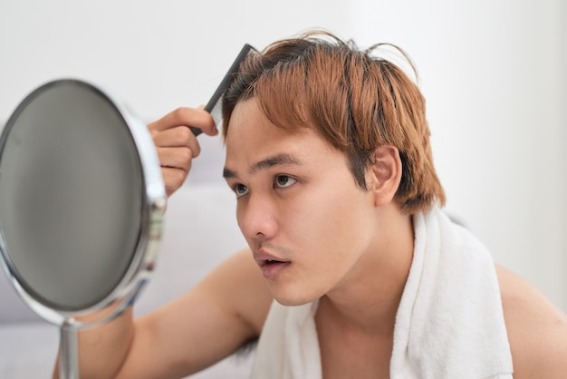 Portrait of handsome man looking at himself in mirror and brushing his hair.