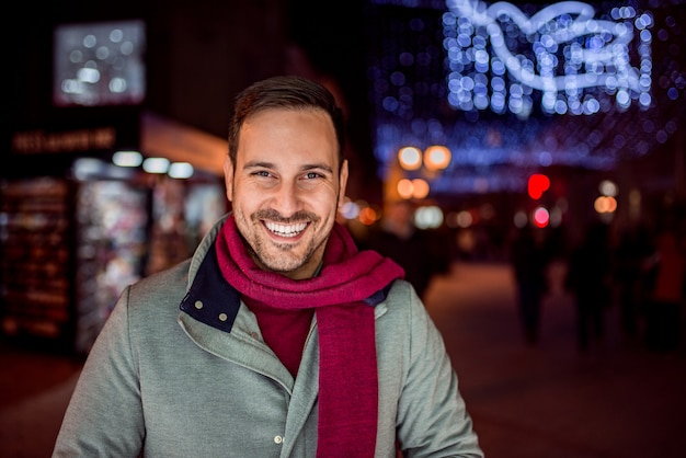 Portrait of a handsome man at night in winter city street.
