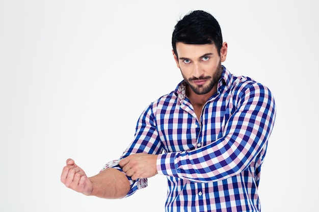 Portrait of a handsome man rolls up his sleeves isolated on a white wall
