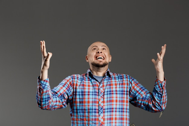 Portrait of handsome man screaming up lifting hands in plaid shirt over grey wall