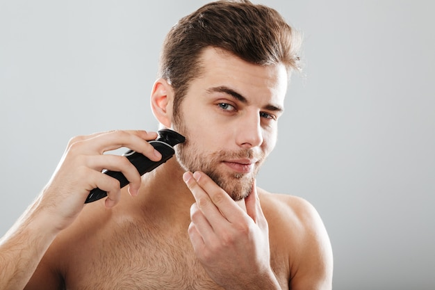Portrait of handsome man shaving his beard with electric shaver in morning against grey wall