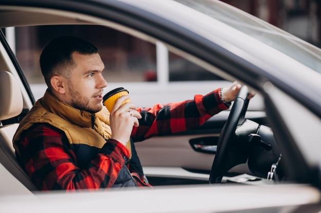 Ritratto di uomo bello seduto in macchina e bere caffè