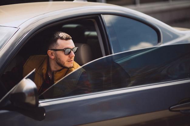 Portrait of handsome man sitting in car