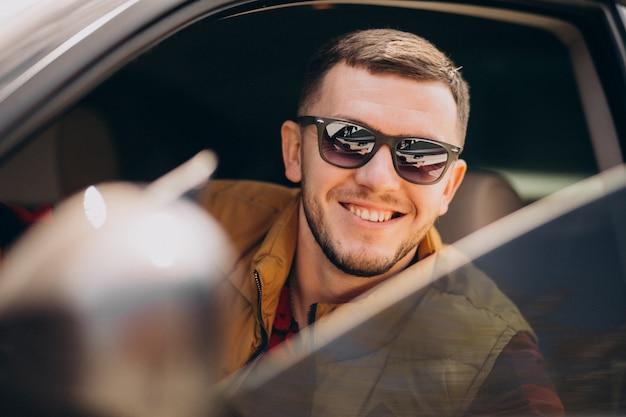 Ritratto di uomo bello seduto in macchina