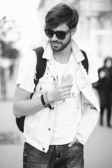 Portrait of handsome man in stylish hipster clothes. attractive guy posing in the street