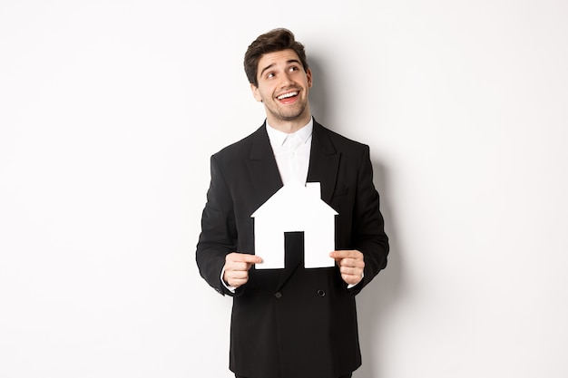 Portrait of handsome man in suit searching for home, holding paper house and looking at upper right corner dreamy, standing over white background.