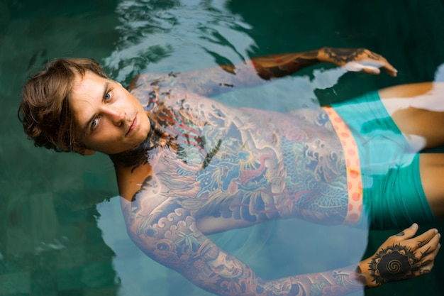 Portrait of a handsome man in tattoos at the pool